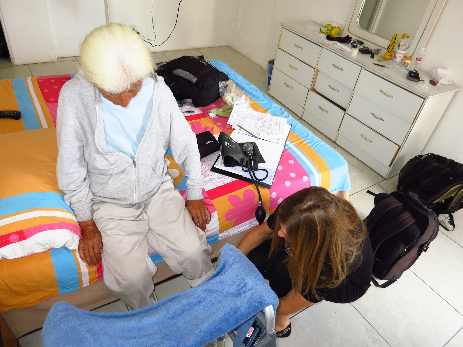 Figure 6.  Physician Assistant, Carrie Kowalski, tends to a patient with mobility issues in a local motel.  Taken by Rose Garcia of The People Concern.