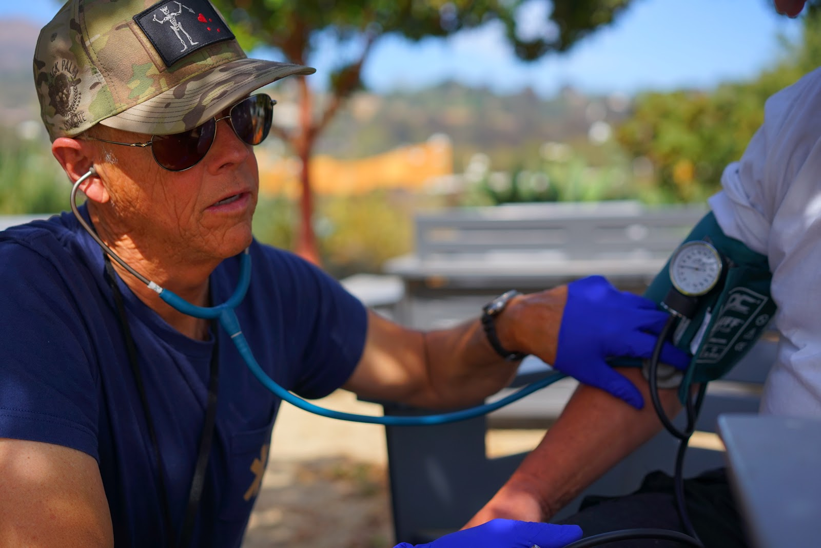 Figure 18.  Peter Miller, street medic, checks vital signs for a patient in the field. Taken by Dr. Coley King of Venice Family Clinic.