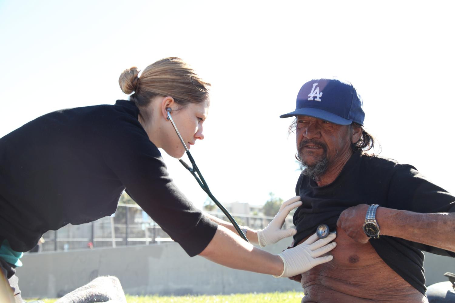 Carrie Kowalski, Physician Assistant, examines a patient at Venice Beach on street medicine rounds in 2012.  Taken by Margaret Molloy.